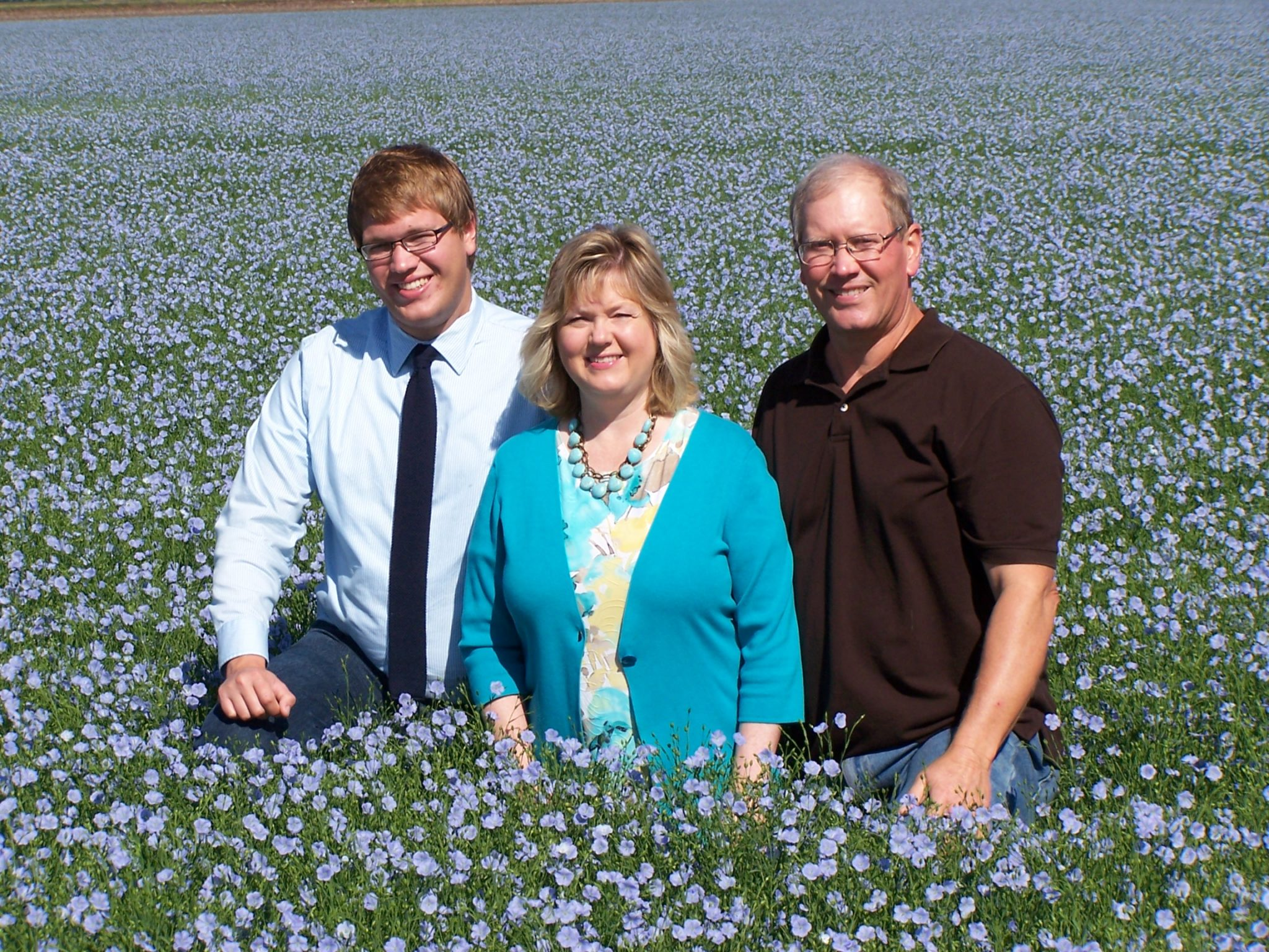 Justin, Esther and Mark Hylden in blooming flax field