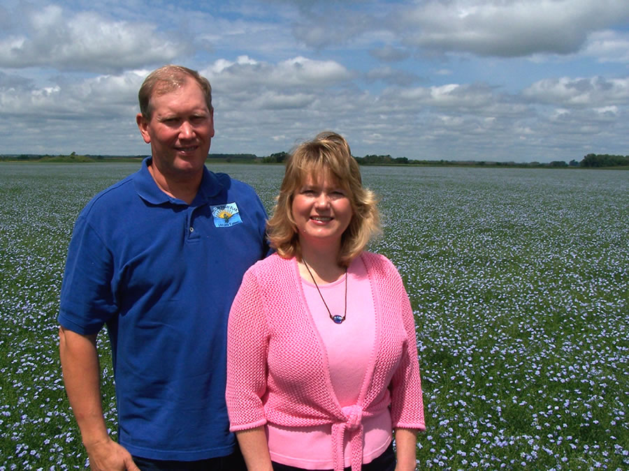 Mark and Esther Hylden in a blooming field of flax